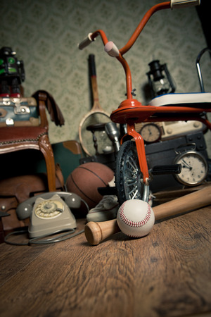 Group of vintage objects on attic hardwood floor, including old toys, phone and sports items. Stock Photo
