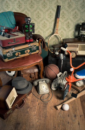 antique tricycle: Group of vintage assorted items on attic hardwood floor with vintage wallpaper background.