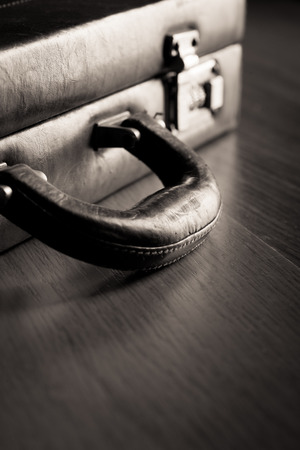 leather briefcase: Leather briefcase lock and handle close-up on dark hardwood floor.