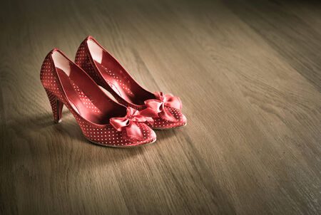 old shoes: Sensual red female shoes on hardwood floor with ribbon and dotted texture.