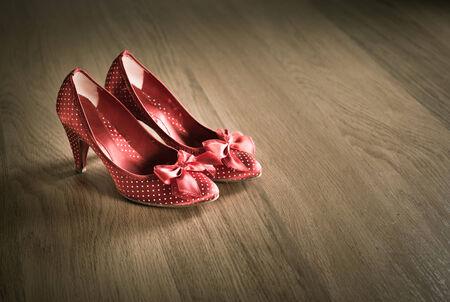 damas antiguas: Sensual zapatos femeninos rojos en piso de madera con la cinta y la textura de puntos. Foto de archivo