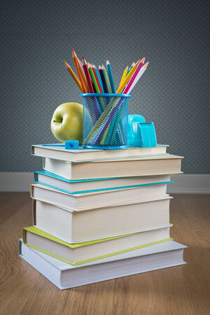Pile of books with color pencils and apple, back to school concept. photo
