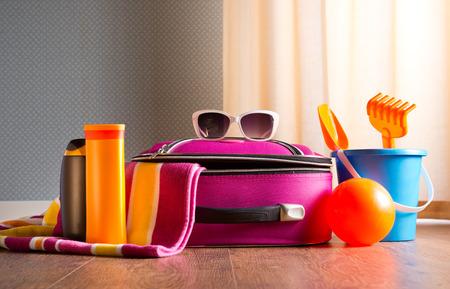 Pink bag, sunglasses, towel, sun creams and beach plastic toys on hardwood floor.