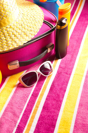 cosmetics bag: Striped colorful towel with pink bag, sunglasses and sun creams. Stock Photo