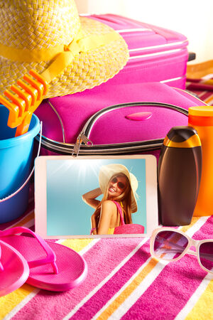 pink hat: Tablet showing vacations pictures with towel, sunglasses, sun creams and beach accessories.