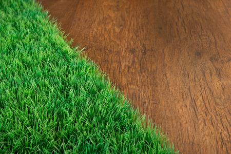 pasto sintetico: Artificial exuberante césped primer plano en el piso de madera de madera.