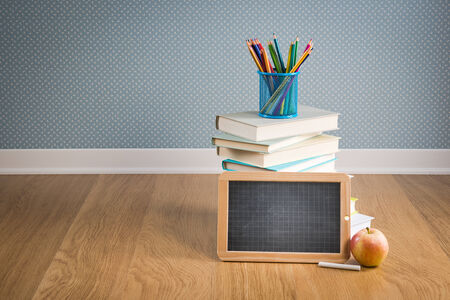 Back to school concept with blackboard, colorful stationery and apple. photo