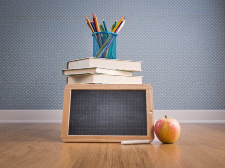 Back to school concept with small chalkboard, apple and colorful stationery. photo