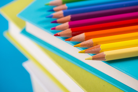 Colorful wooden pencils on a pile of books against light blue background. photo
