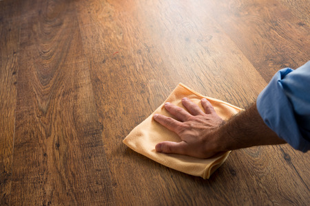 Mannelijke hand reinigen en wrijven een hardhouten vloer met een microfiber doek. Stockfoto
