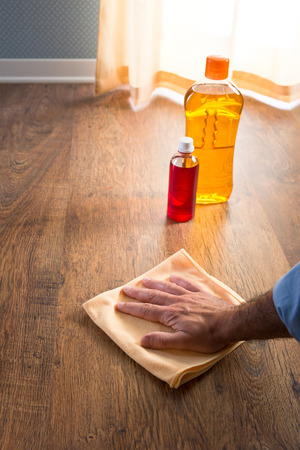 disinfecting: Male hand applying wood care products on hardwood floor surface with a microfiber cloth. Stock Photo