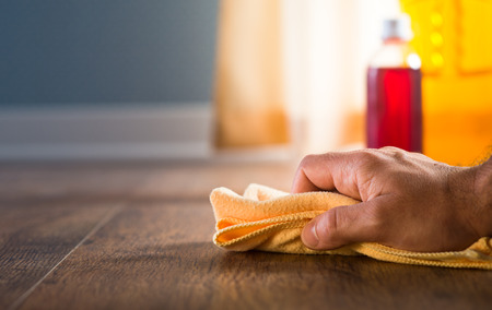 cleaning floor: Male hand applying wood care products and cleaners on hardwood floor surface.