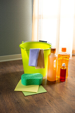 disinfecting: Wood cleaners and detergents on floor with bucket, gloves, cloth and sponges. Stock Photo