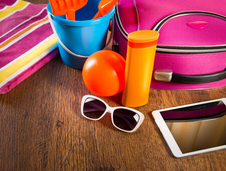 leaving: Leaving for vacations on the beach with digital tablet and colorful luggage and accessories. Stock Photo