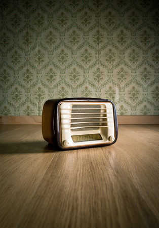Old vintage radio on hardwood floor with retro wallpaper on background. photo