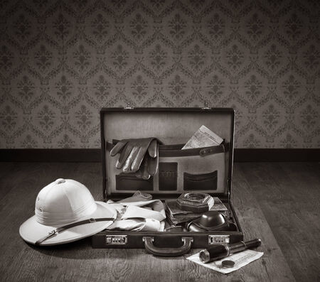 open suitcase: Colonial style explorer packing with open leather briefcase, pith hat, leather gloves, maps and brass telescope.