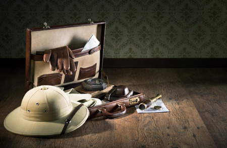pith: Colonial style explorer packing with open leather briefcase, pith hat, leather gloves, maps and brass telescope.