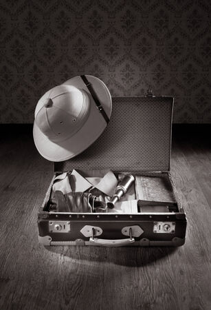 pith: Open suitcase with colonial style explorer equipment including pith helmet, old books and brass telescope.