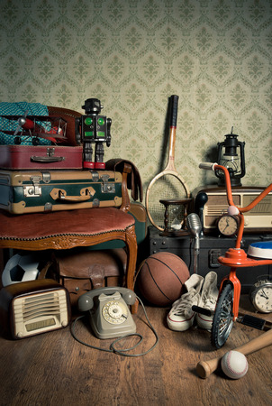 antique tricycle: Assorted vintage items in the attic with retro wallpaper background. Stock Photo
