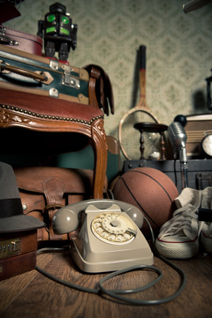 Group of vintage objects on attic hardwood floor, including old toys, phone and sports items. photo