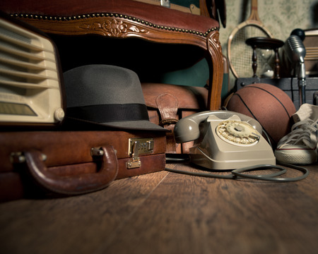 old items: Group of vintage objects on attic hardwood floor, including old toys, phone and sports items. Stock Photo
