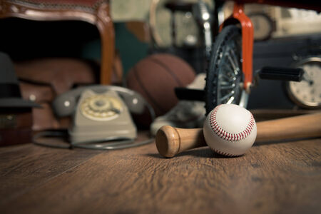 antique tricycle: Group of vintage objects on attic hardwood floor, including old toys, phone and sports items. Stock Photo