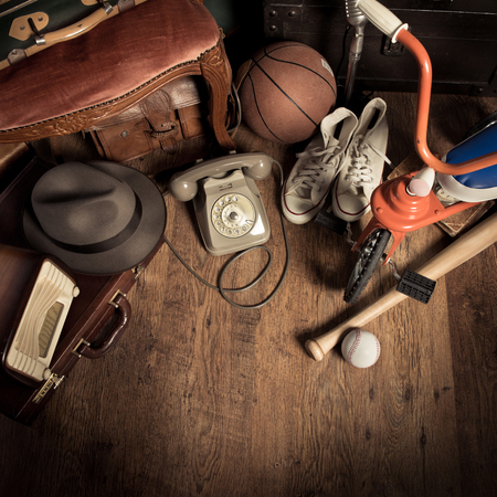 Group of assorted vintage items on hardwood floor at flea market. Stock Photo
