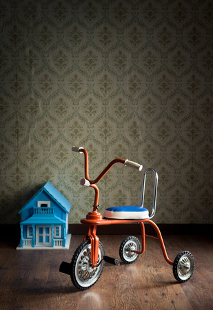 doll house: Vintage tricycle with doll house on background and vintage wallpaper.