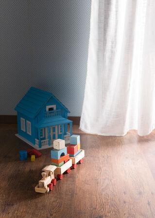 juguetes antiguos: Casa de muñecas y tren de juguete de madera en el piso de madera al lado de una ventana.