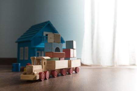 juguetes antiguos: Casa de mu�ecas y tren de juguete de madera en el piso de madera al lado de una ventana.