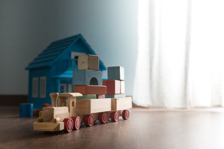doll house: Doll house and wooden toy train on hardwood floor next to a window. Stock Photo