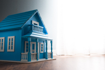 doll house: Blue wooden model house next to a window with curtain on wooden floor. Stock Photo
