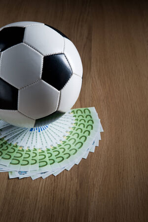 pelota de futbol: Bal�n de f�tbol con ventilador de billetes en euros en el piso de madera dura.