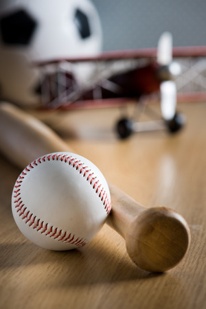 hardball: Baseball bat and hardball on wooden floor with toy plane and soccer ball on background.