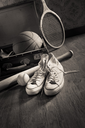 Vintage suitcase with sports equipment on wooden floor with canvas shoes on foreground. photo