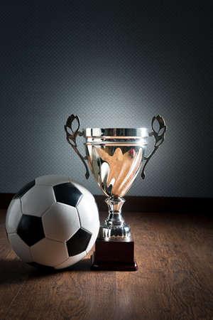 pelota de futbol: Trofeo de la Copa de Oro y el bal�n de f�tbol en el piso de madera, concepto ganador.
