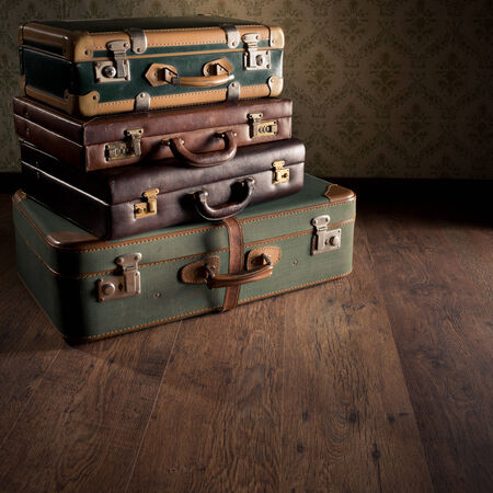 old suitcase: Stack of colorful vintage suitcases on hardwood floor, travelling concept. Stock Photo