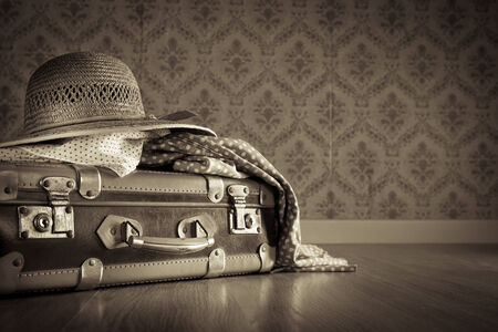 packing suitcase: Holiday packing with vintage suitcase and polka dot clothing on hardwood floor. Stock Photo