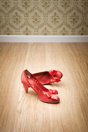 red shoes: Vintage red dotted female shoes with ribbon on hardwood floor with retro wallpaper on background.
