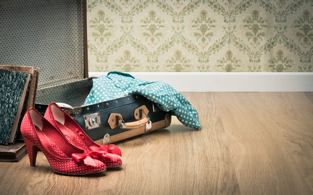 open suitcase: Open vintage suitcase with red shoes and dotted clothing, vintage wallpaper on background.