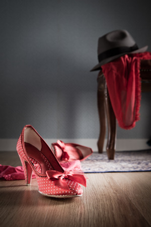Female and male shoes, lingerie and male hat on chair and floor, romance and sensuality concept. photo