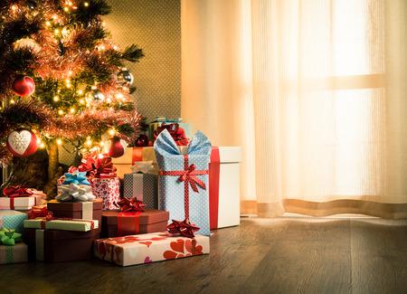 Elegant christmas tree with decorations and gifts on elegant hardwood floor. Archivio Fotografico