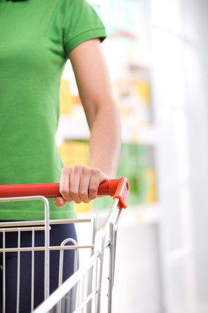 necessities: Young woman with trolley at store hands close-up. Stock Photo