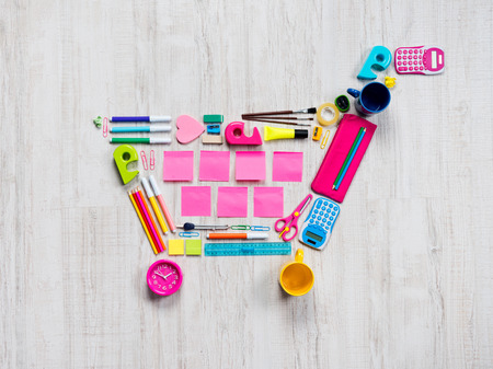 composed: Colorful shopping cart composed of stationery and office objects. Stock Photo