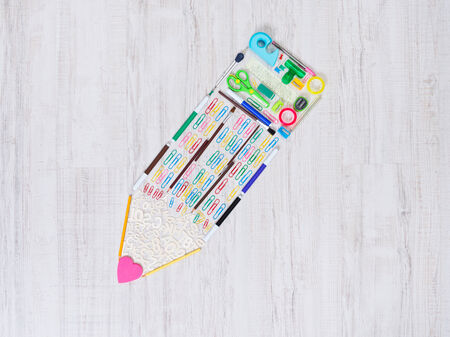 back view student: Creative pencil composed of colorful stationery items on the floor.