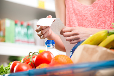 Unrecognizable woman checking a long supermarket receipt with grocery on foreground. Stock Photo