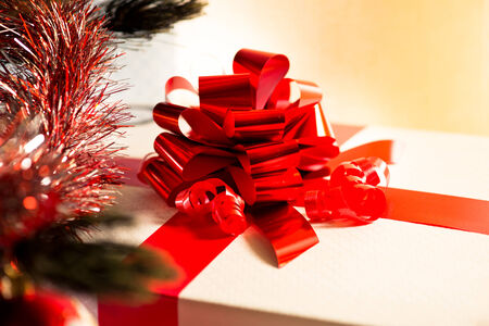 Elegant Christmas gift with red ribbon and fir decorated branch. photo