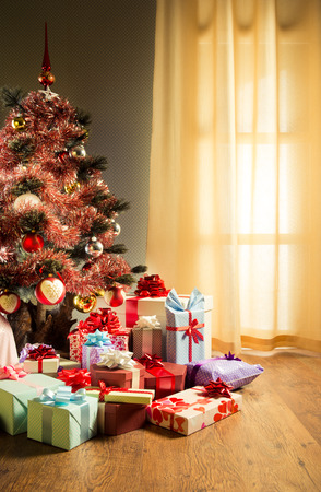 christmas  eve: Colorful gifts in front of an elegant christmas tree in the living room.