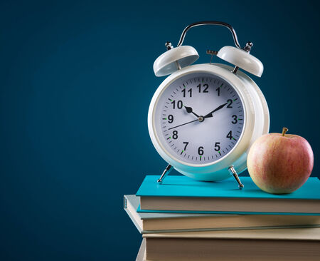 Back to school concept with pile of books, apple and vintage alarm clock. photo