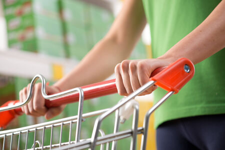 cart: Woman in green t-shirt pushing a shopping cart at store with shelves on background. Stock Photo